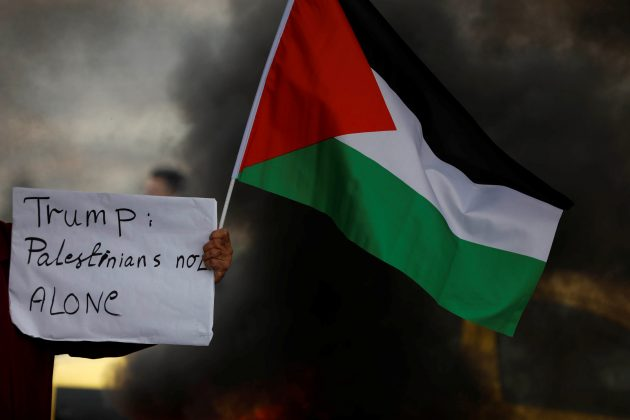 A demonstrator holds a sign and a Palestinian flag during clashes with Israeli troops at a protest against U.S. President Donald Trump's decision to recognise Jerusalem as the capital of Israel, near the West Bank city of Nablus, December 29, 2017.