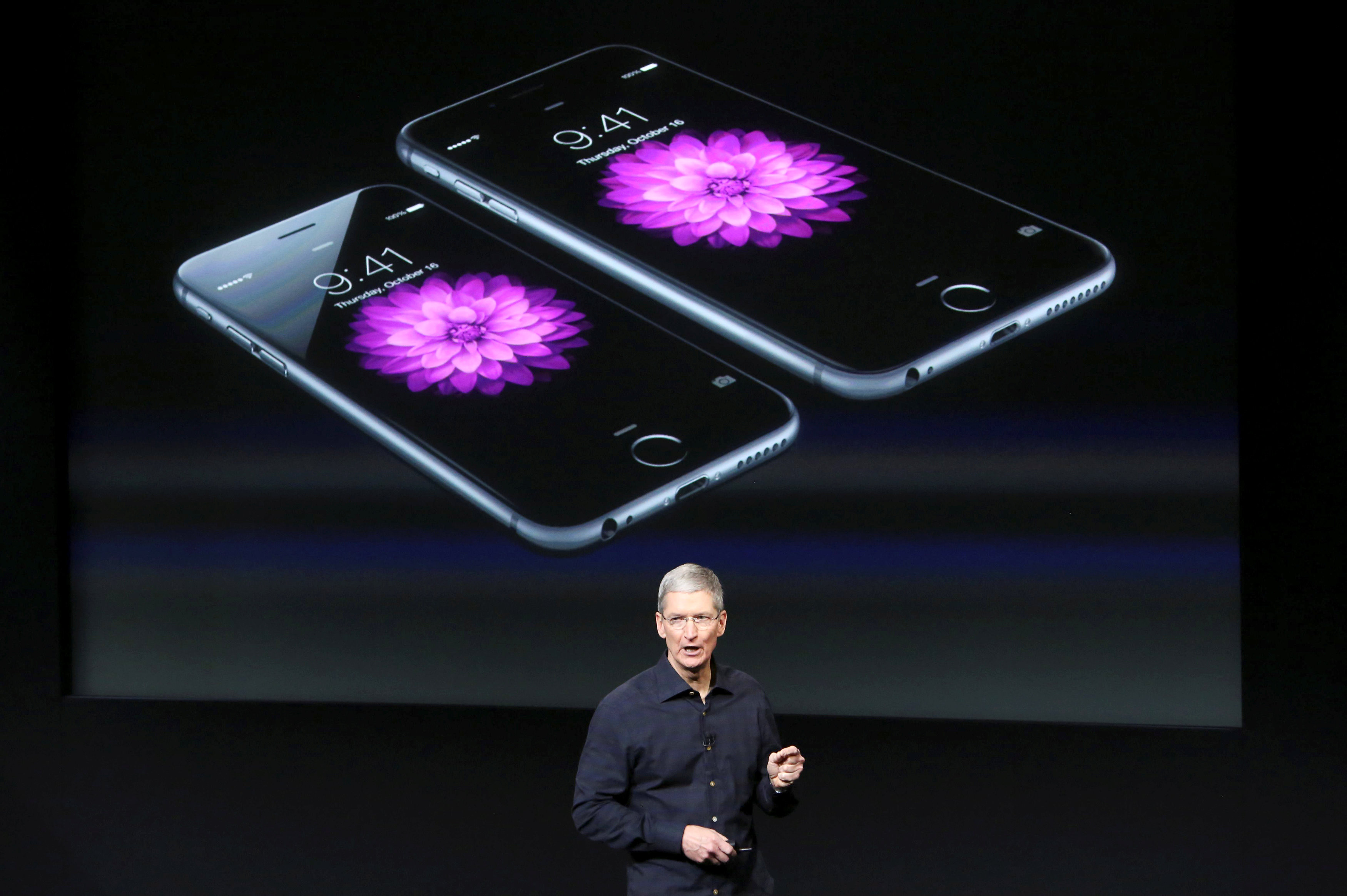 Apple CEO Tim Cook stands in front of a screen displaying the IPhone 6 during a presentation at Apple headquarters in Cupertino, California October 16, 2014.