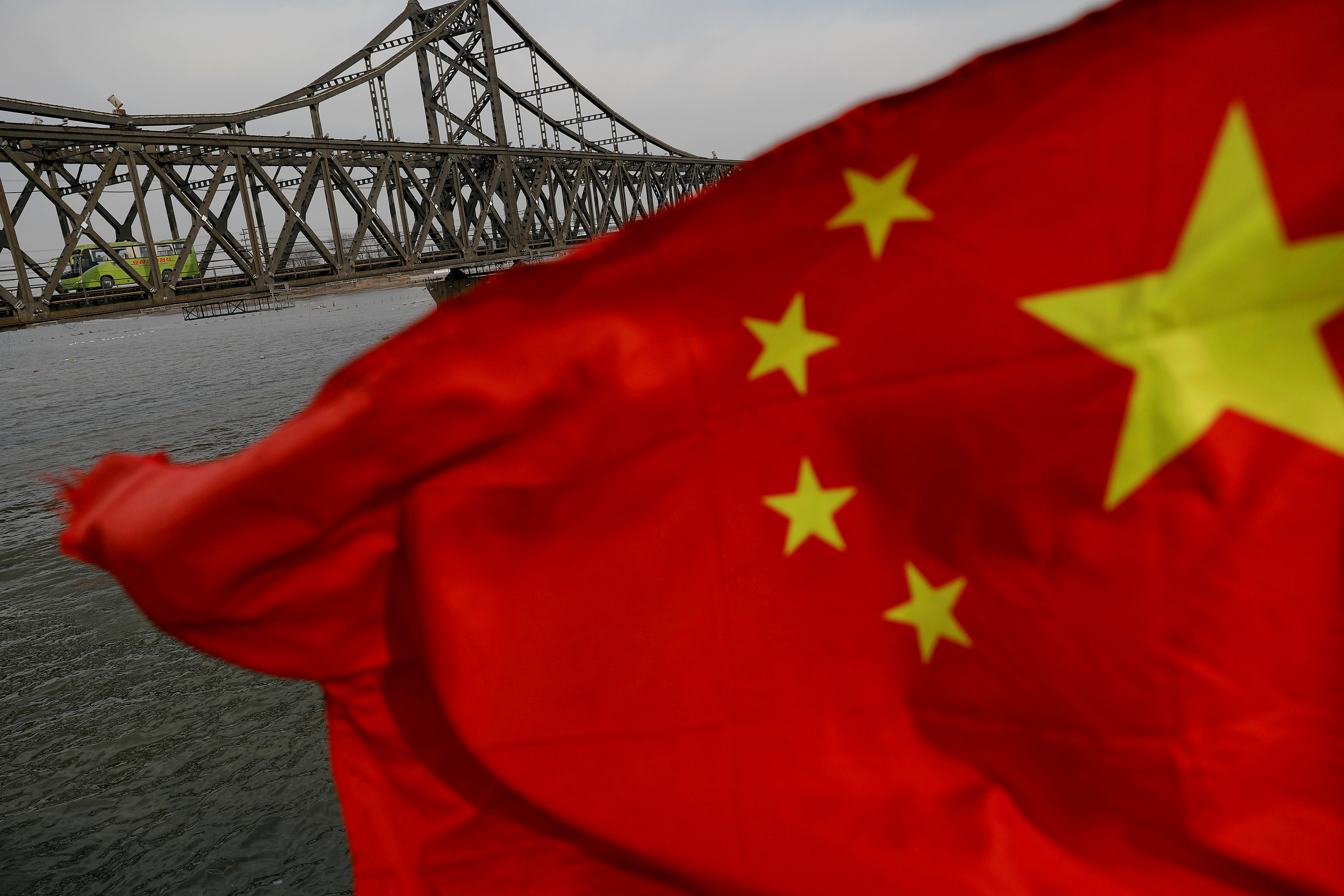 : A Chinese flag is seen in front of the Friendship bridge over the Yalu River connecting the North Korean town of Sinuiju and Dandong in China's Liaoning Province on April 1, 2017.