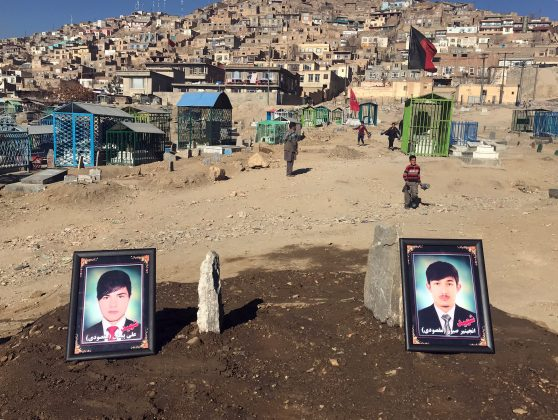 The photos of two brothers, who were killed during yesterday's suicide attack at a Shi'ite cultural centre, are seen on their graves in Kabul, Afghanistan. December 29, 2017.