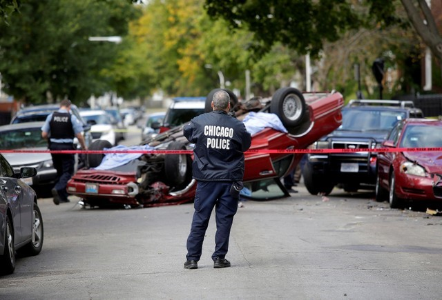 Chicago Police officers investigate a crime scene after a motorist was shot in the head and lost control of his vehicle along the 5300 block of west Monroe Street in Chicago, Illinois, U.S., October 31, 2017. The driver later died in the hospital, according to the police.