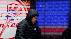 A man walks in falling snow at Times Square as a cold weather front hits the region, in Manhattan, New York, U.S., December 30, 2017.