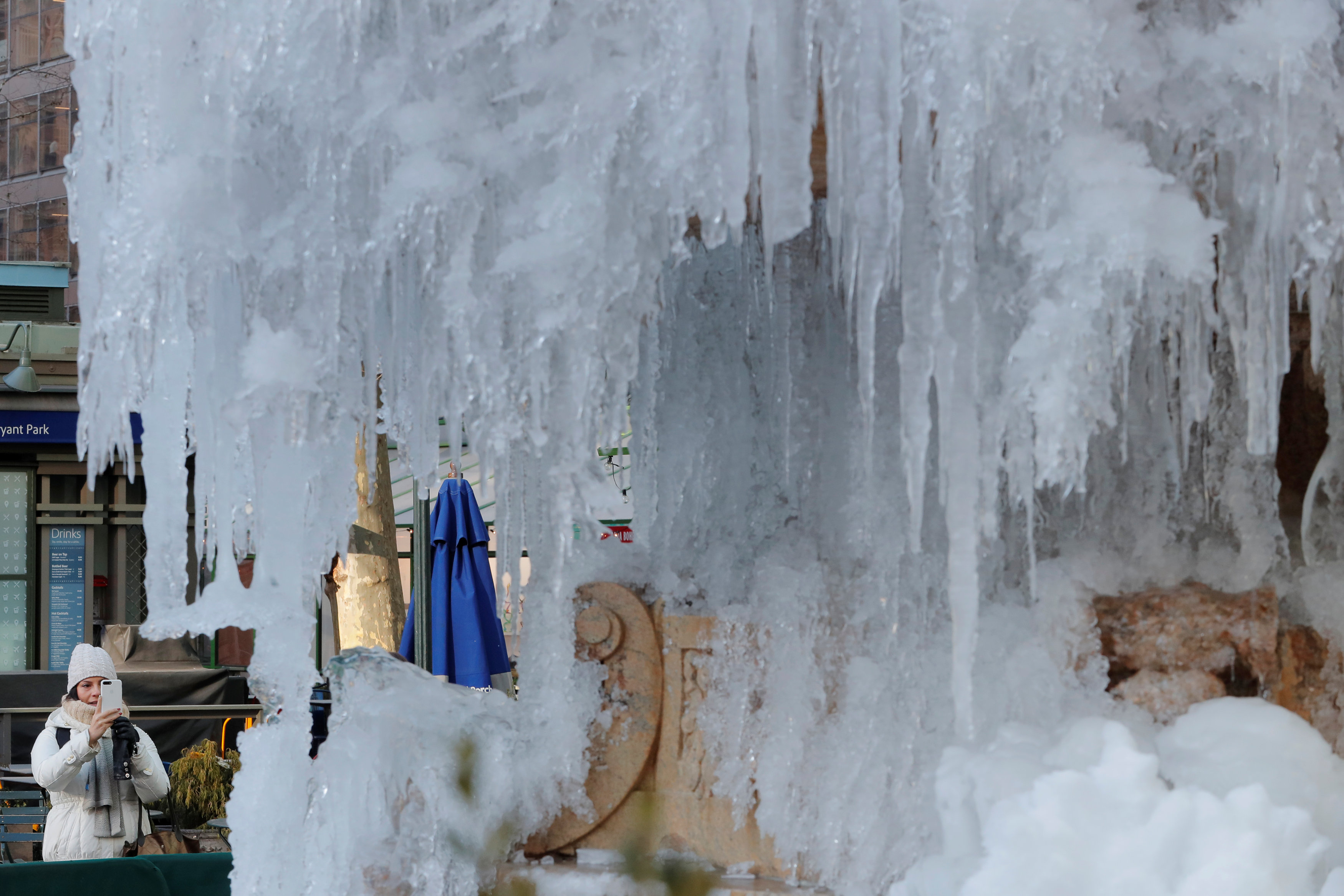A woman stops to photograph the frozen Josephine Shaw Lowell Memorial Fountain in New York, U.S., January 3, 2018.