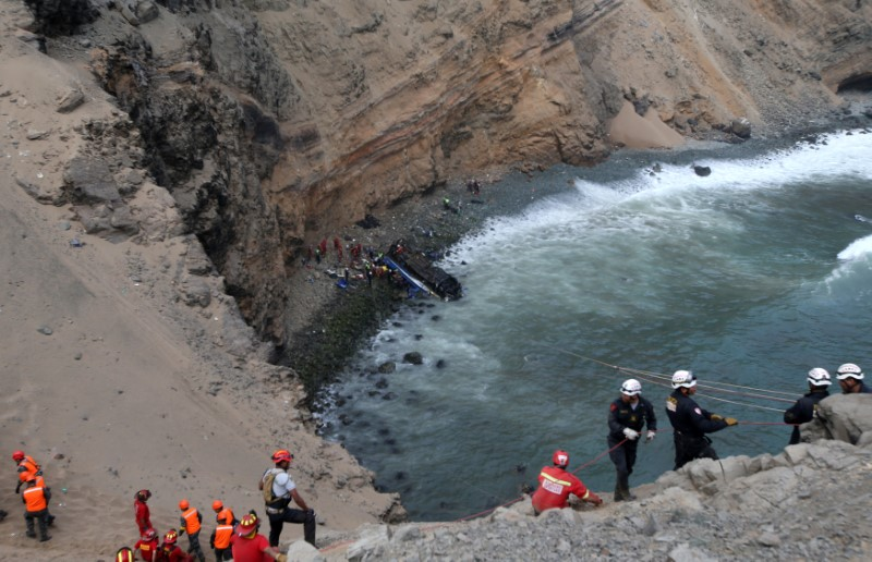 Rescue workers and police work at the scene after a bus crashed with a truck and careened off a cliff along a sharply curving highway north of Lima, Peru, January 2, 2018. REUTERS/Guadalupe Pardo