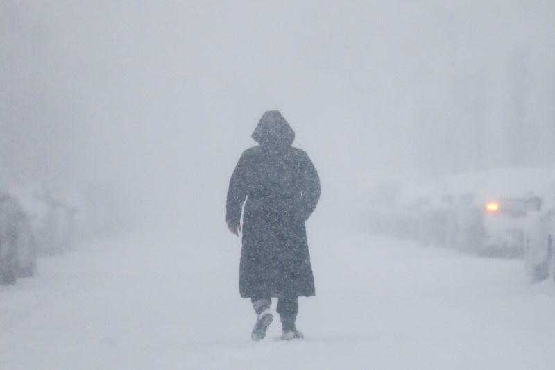 A woman walks down the street during a blizzard in Long Beach, New York, U.S. January 4, 2018.