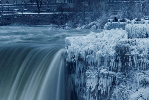 A lone visitor takes a picture near the brink of the ice covered Horseshoe Falls in Niagara Falls, Canada.