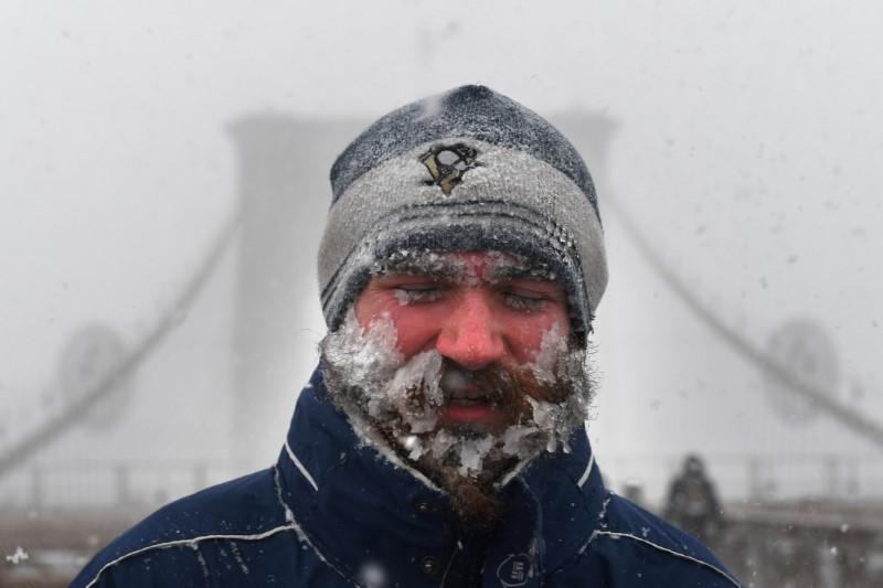 A pedestrian walks through blinding snow across the Brooklyn Bridge in New York City.
