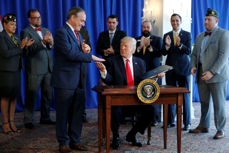 President Donald Trump shakes hands with Secretary of Veterans Affairs David Shulkin (L) after signing the Veterans Affairs Choice and Quality Employment Act at Trump's golf estate in Bedminster, New Jersey U.S. August 12, 2017.