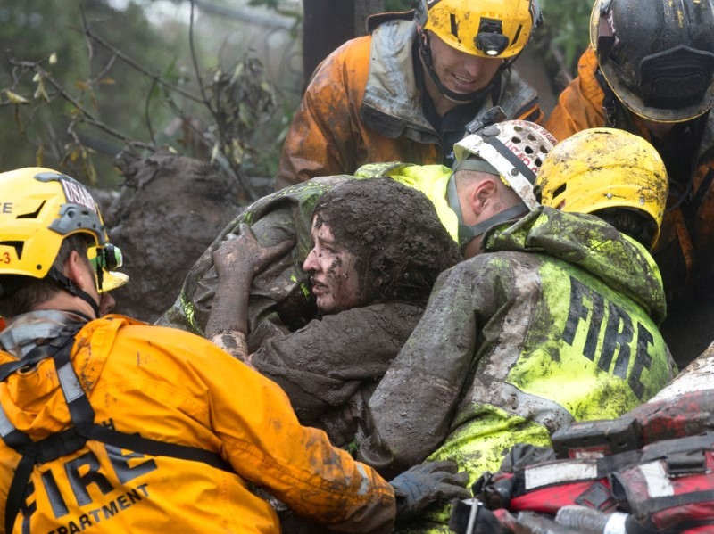 Emergency personnel carry a woman rescued from a collapsed house after a mudslide in Montecito, California, U.S. January 9, 2018.