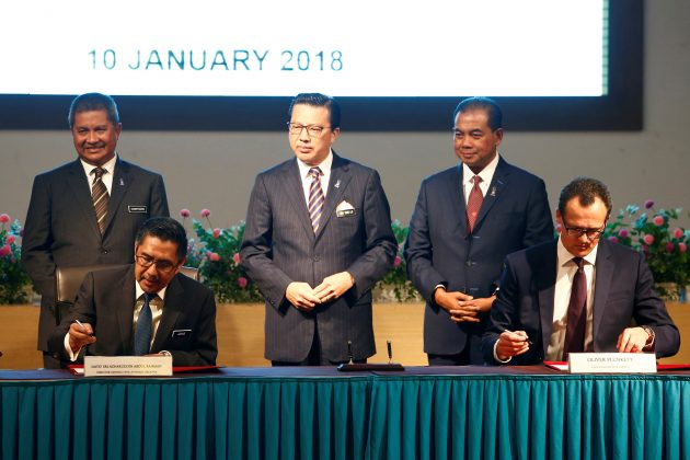 Civil Aviation Malaysia's Director General Azharuddin Abdul Rahman and Ocean Infinity's CEO Oliver Plunkett sign documents, witnessed by Malaysia's Transport Minister Liow Tiong Lai, during the MH370 search operations signing ceremony between Malaysia's government and Ocean Infinity, in Putrajaya, Malaysia January 10,