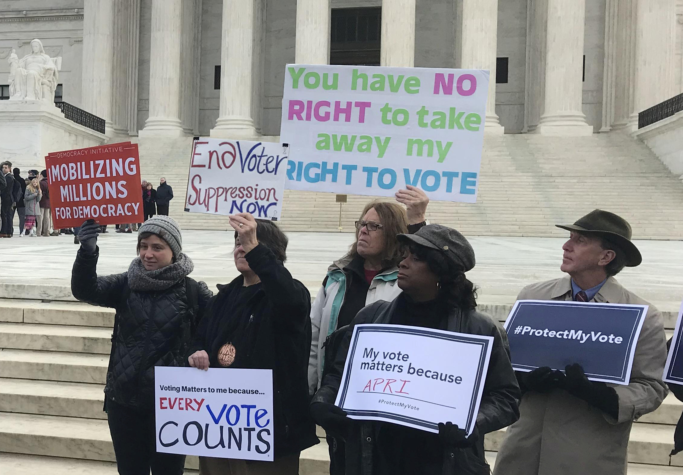 Activists rally outside the U.S. Supreme Court ahead of arguments in a key voting rights case involving a challenge to the OhioÕs policy of purging infrequent voters from voter registration rolls, in Washington, U.S., January 10, 2018.