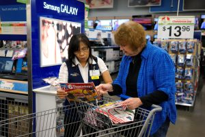 A Walmart employee helps a customer navigate a flyer at the store in Broomfield, Colorado November 28, 2014.