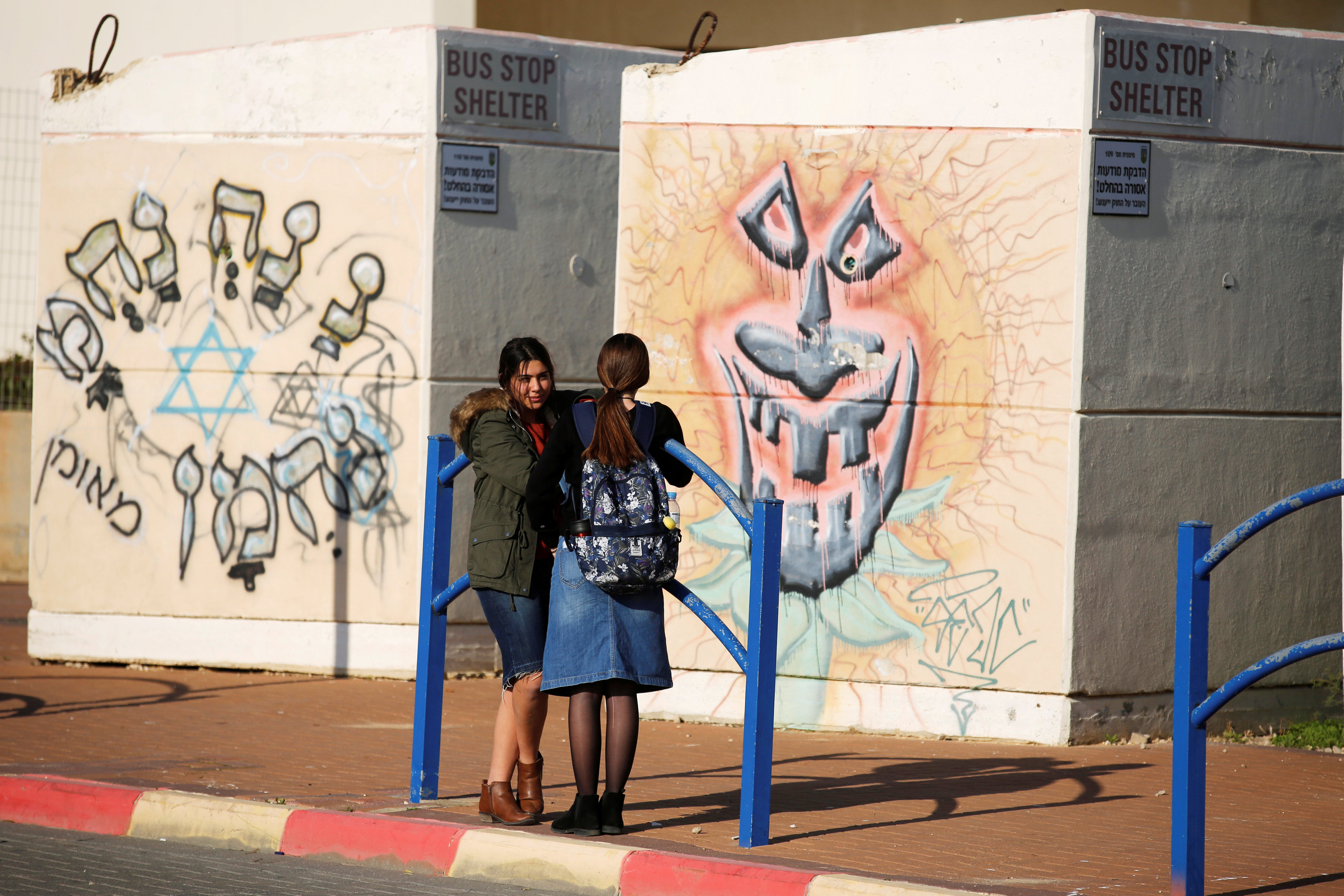 Schoolgirls stand next to bus stop bomb shelters in the southern Israeli city of Sderot, close to the Israeli border with the Gaza Strip January 8, 2018.