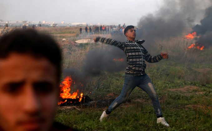 A Palestinian demonstrator hurls stones towards Israeli troops during clashes, near the border with Israel in the east of Gaza City January 12, 2018.