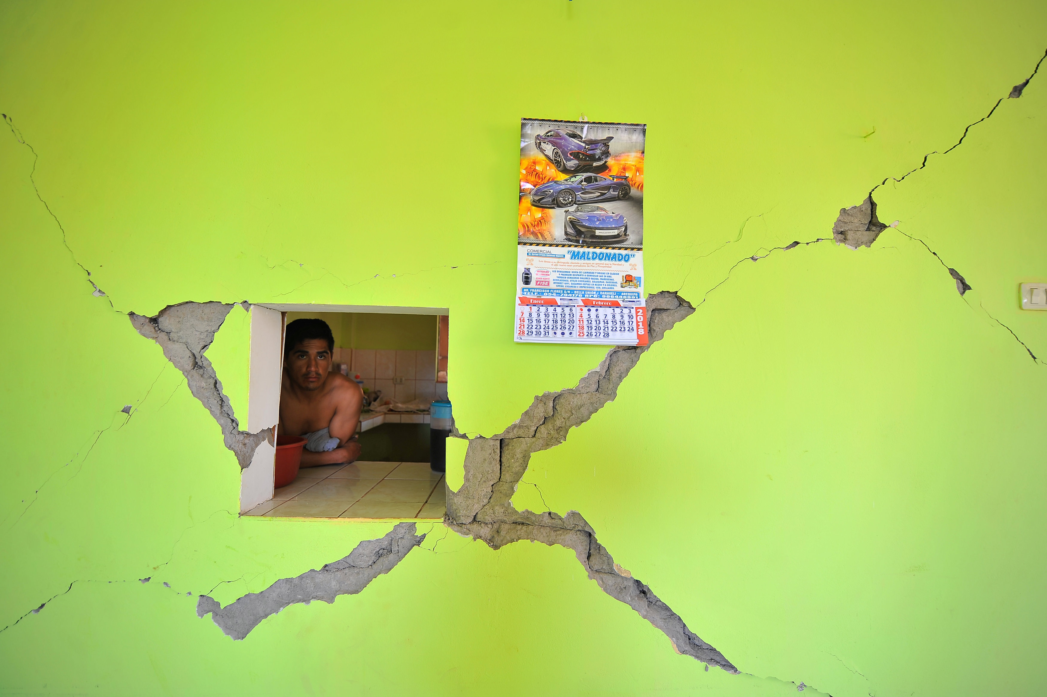 A man observes a damage building after a strong magnitude 7.1 earthquake struck the coast of southern Peru, in Acari, Arequipa , Peru, January 14, 2018.