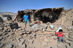 A man and a child stand at debris of a building after a strong magnitude 7.1 earthquake struck the coast of southern Peru, in Acari, Arequipa , Peru, January 14, 2018.