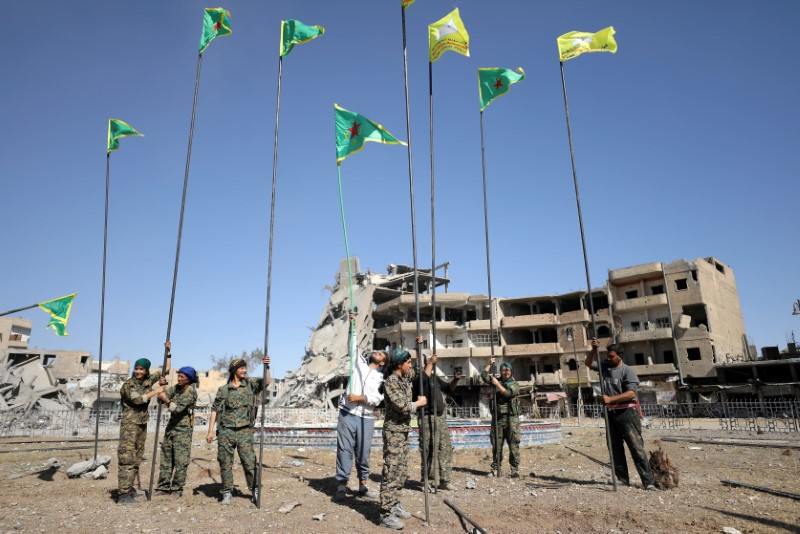 Fighters of Syrian Democratic Forces place flags at Naim Square after liberating Raqqa, Syria October 18, 2017.