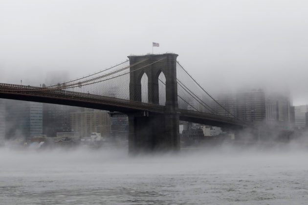 The Brooklyn Bridge is seen partially in fog from in front of the Manhattan skyline in Brooklyn, New York, U.S., January 12, 2018.