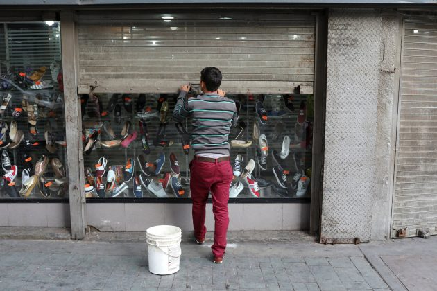 A worker closes the security shutter of a window display at a shoes store in downtown Caracas, Venezuela January 16, 2018.