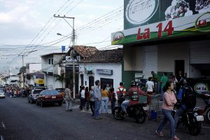 People line up outside a supermarket with its security shutters partially closed as a precaution against riots or lootings, in San Cristobal, Venezuela January 16, 2018.