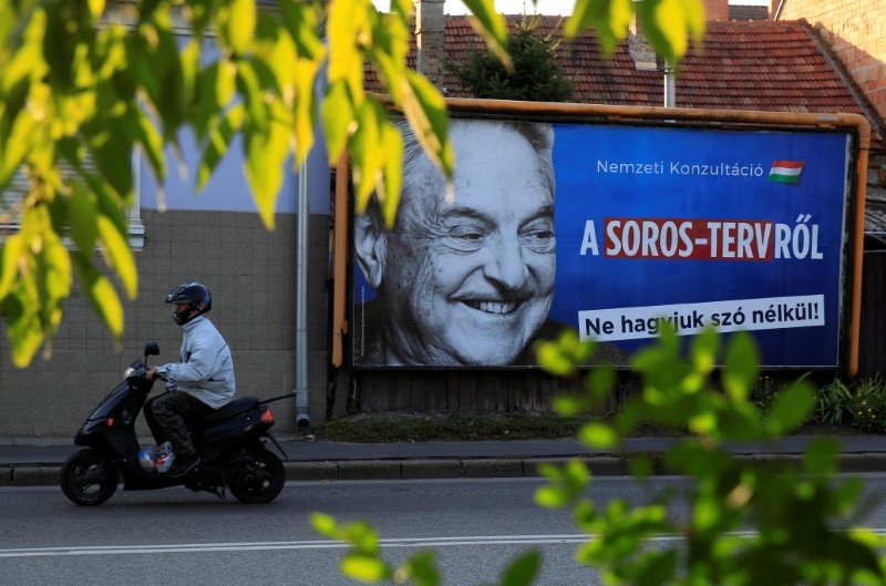 : A man rides his moped past a government billboard displaying George Soros in monochrome next to a message urging Hungarians to take part in a national consultation about what it calls a plan by the Hungarian-born financier to settle a million migrants in Europe per year, in Szolnok, Hungary, October 2, 2017.