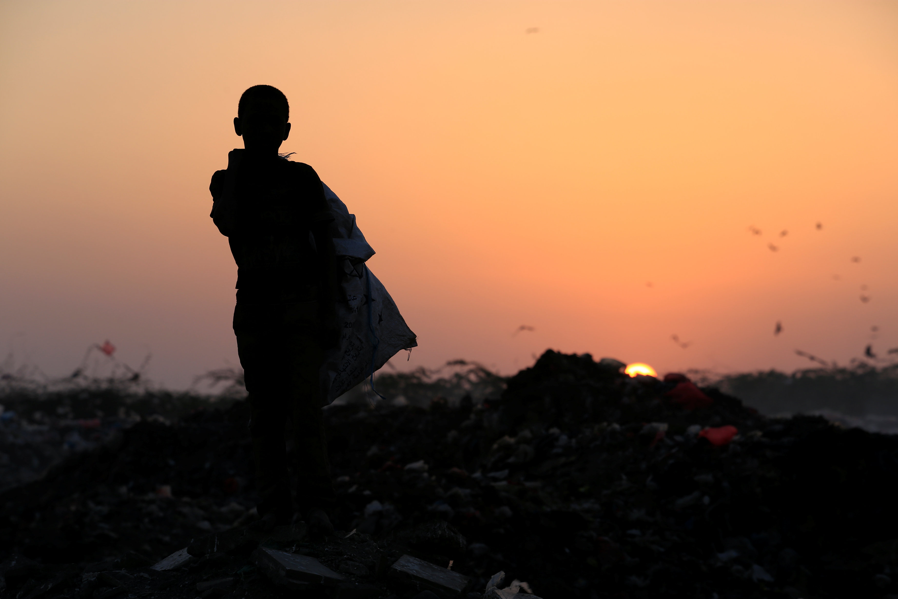 Ayoub Mohammed Ruzaiq, 11, stands in a garbage dump where he collects recyclables and food near the Red Sea port city of Hodeidah, Yemen, January 13, 2018.