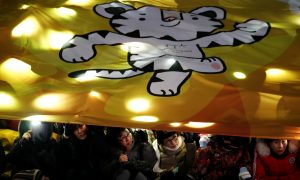 Women watch the Olympic torch relay under a giant banner depicting the 2018 PyeongChang Winter Olympics mascot Soohorang, in Seoul, South Korea, January 13, 2018.