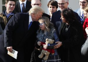 U.S. President Donald Trump greets a young girl among families gathered in the White House Rose Garden as he addresses the annual March for Life rally, taking place on the nearby National Mall in Washington, U.S., January 19, 2018.