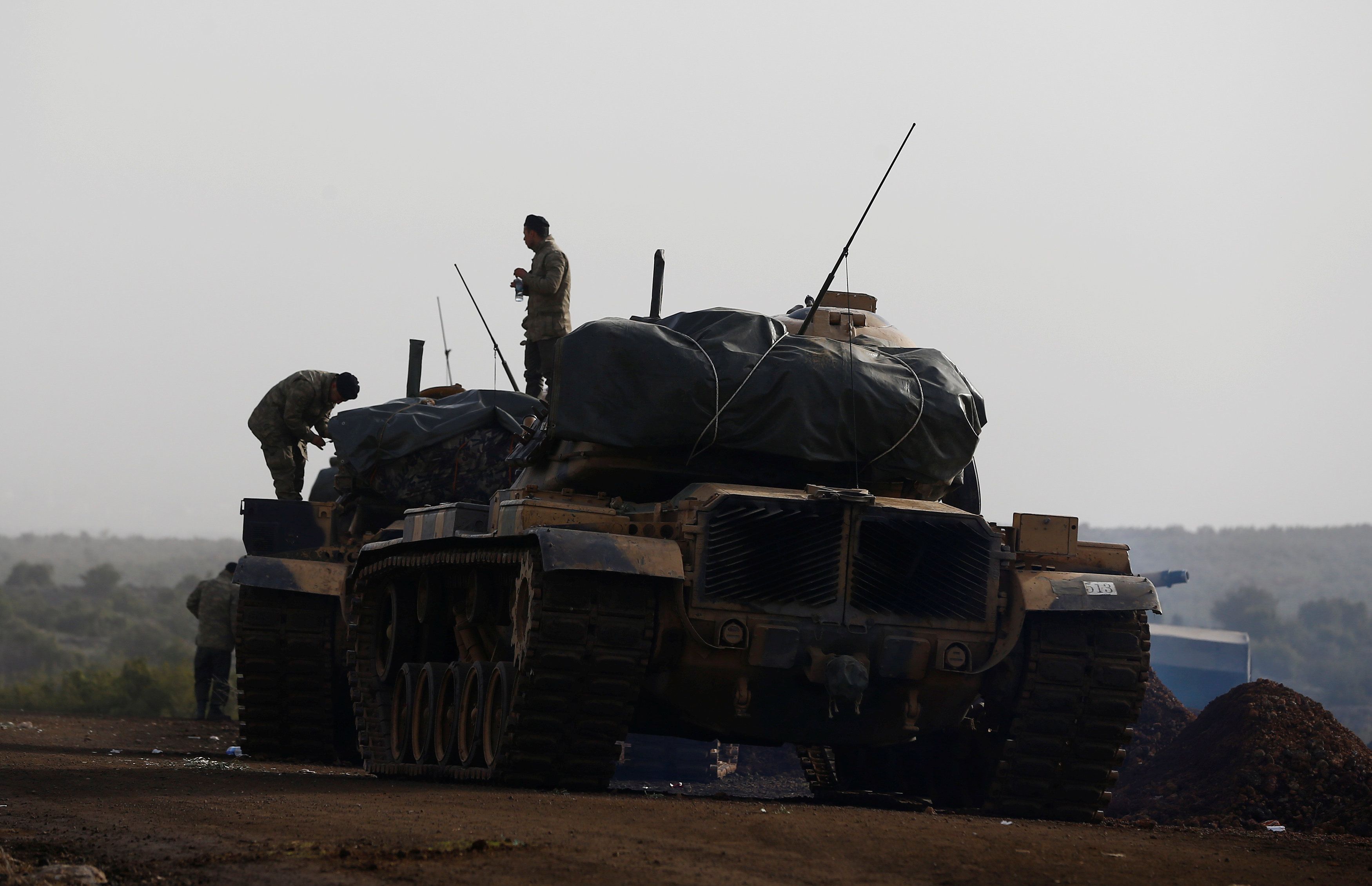 Turkish soldiers stand on tanks in a village on the Turkish-Syrian border in Gaziantep province, Turkey January 22, 2018.