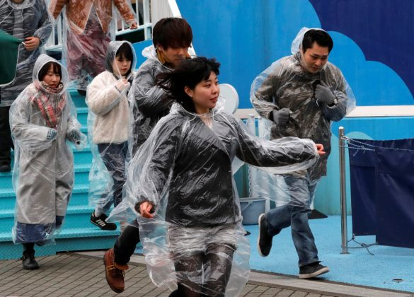 Participants run during an anti-missile evacuation drill at the Tokyo Dome City amusement park in Tokyo, Japan January 22, 2018.