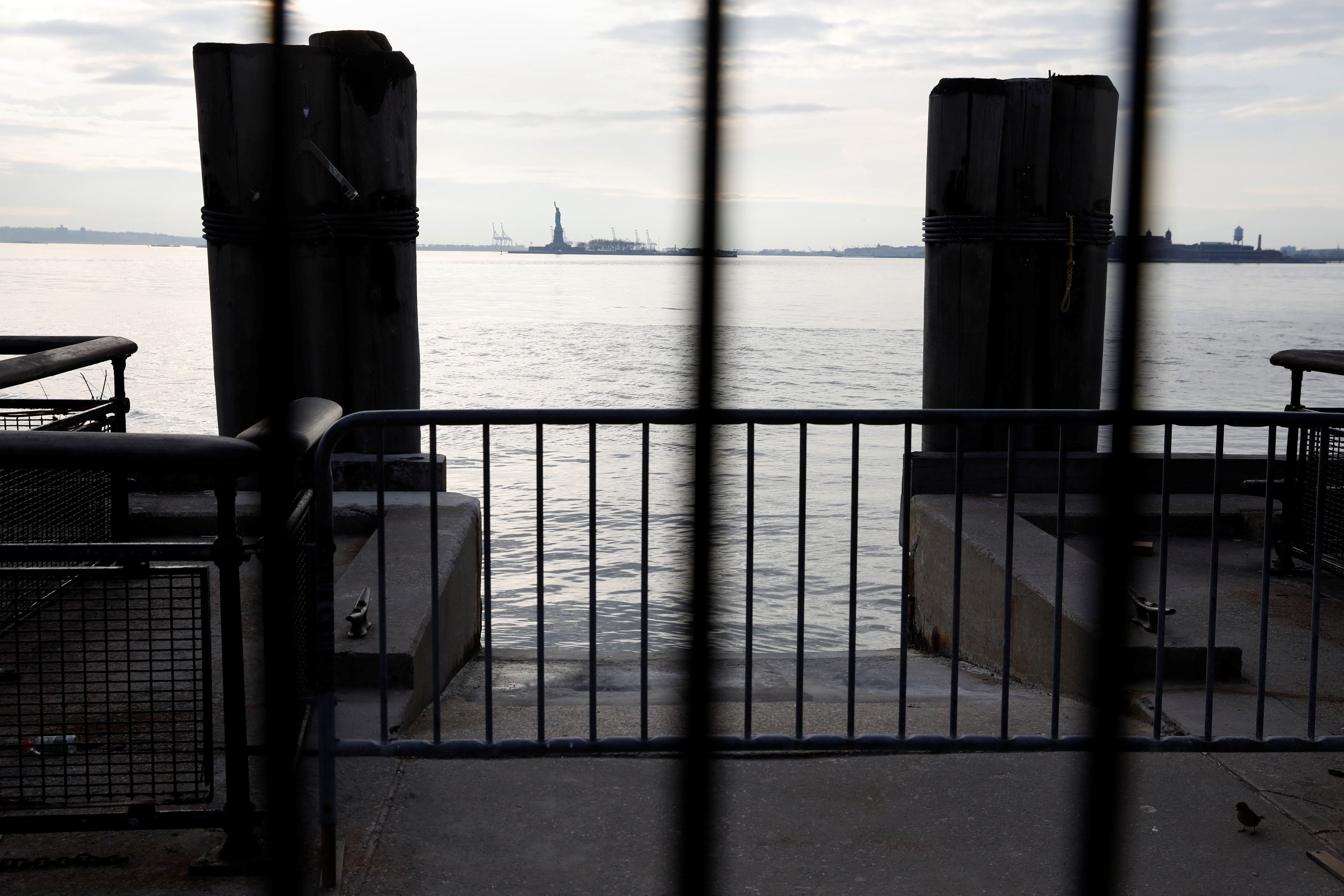 The Statue of Liberty is seen through fencing from a ferry dock following a U.S. government shutdown in Manhattan, New York, U.S., January 21, 2018.