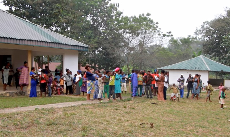 A still image taken from a video shot on December 9, 2017 shows Cameroonian refugees standing outside a center in Agbokim Waterfalls village, which borders on Cameroon, Nigeria.