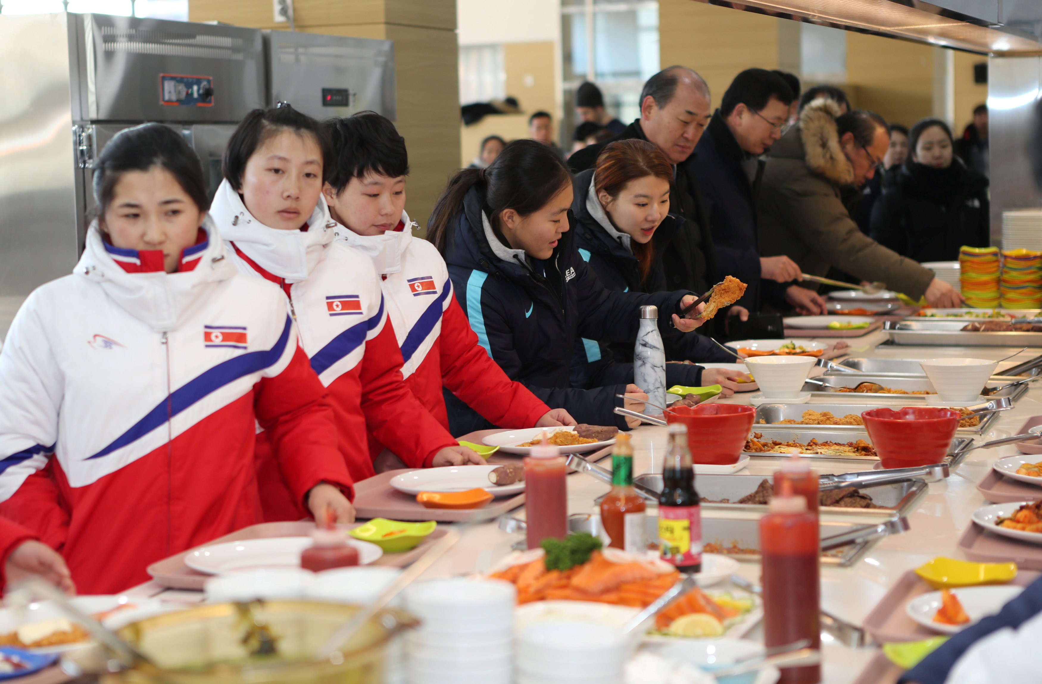 North and South Korea women's ice hockey athletes stand in a line at a dining hall at the Jincheon National Training Centre in Jincheon, South Korea January 25, 2018
