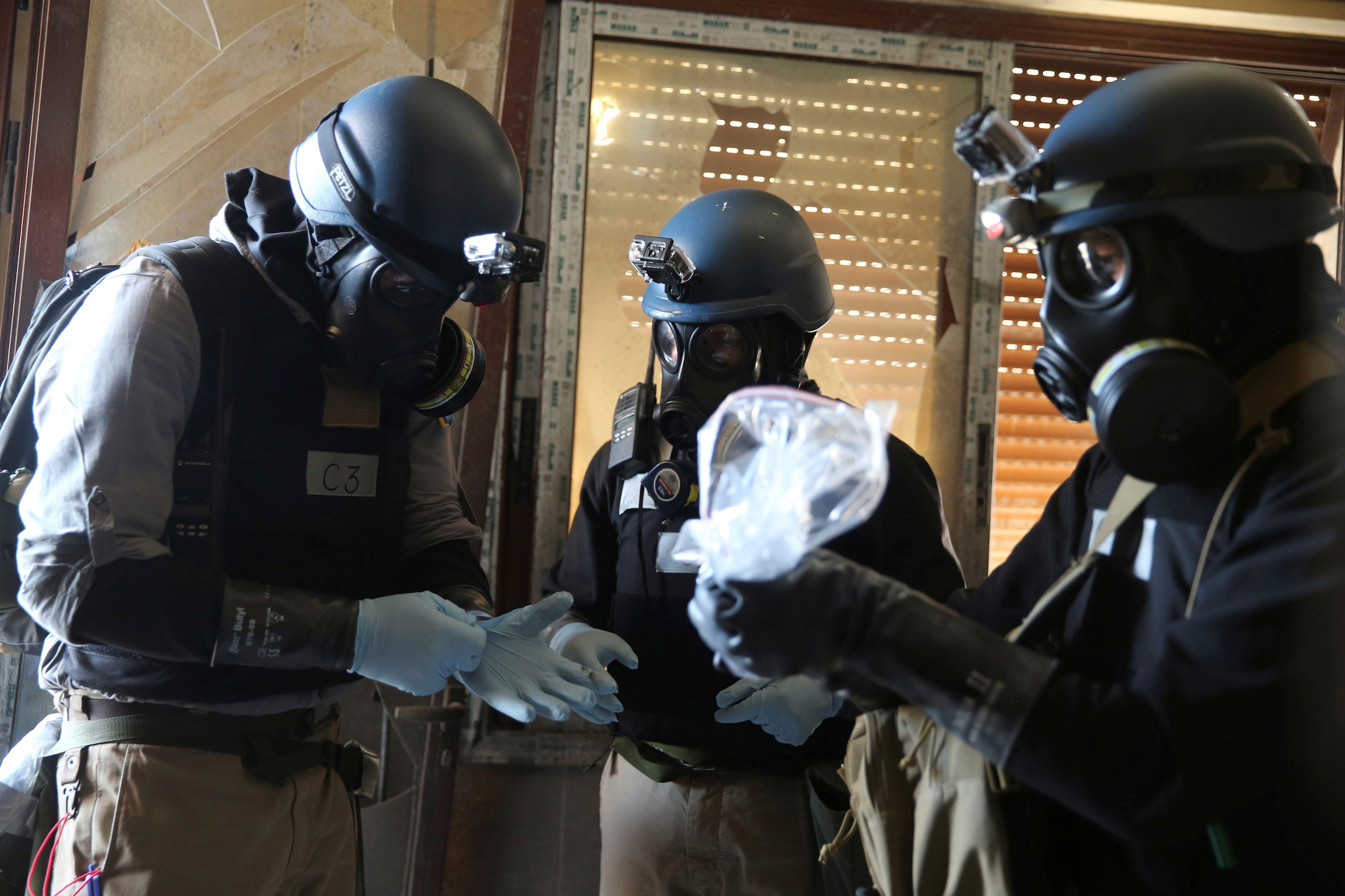 A U.N. chemical weapons expert, wearing a gas mask, holds a plastic bag containing samples from one of the sites of an alleged chemical weapons attack in the Ain Tarma neighbourhood of Damascus, Syria August 29, 2013.
