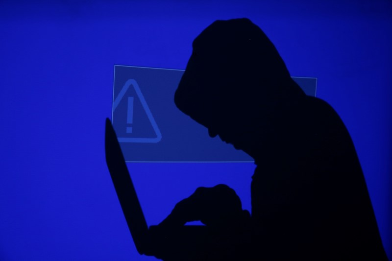 A hooded man holds a laptop computer as blue screen with an exclamation mark is projected on him in this illustration picture taken on May 13, 2017.