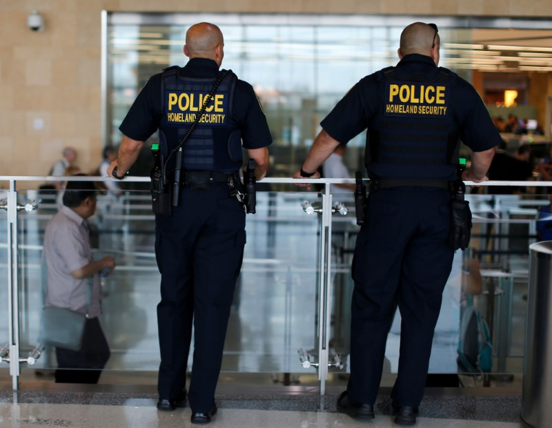 Homeland Security personnel keep watch as travelers depart at Lindbergh Field airport in San Diego, California, U.S. July 1, 2016.