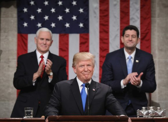 U.S. President Donald J. Trump (C) stands at the podium as U.S. Vice President Mike Pence (L) and Speaker of the House U.S. Rep. Paul Ryan (R-WI) (R) look on during his first State of the Union address to a joint session of Congress inside the House Chamber on Capitol Hill in Washington, U.S., January 30, 2018.