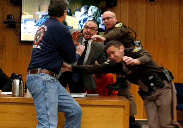Randall Margraves (L) lunges at Larry Nassar,(wearing orange) a former team USA Gymnastics doctor who pleaded guilty in November 2017 to sexual assault charges, during victim statements of his sentencing in the Eaton County Circuit Court in Charlotte, Michigan, U.S., February 2, 2018.