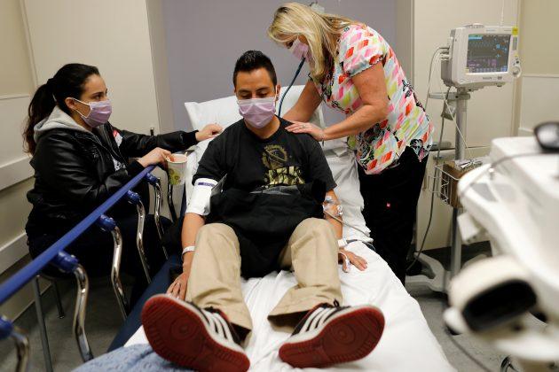 Emergency room nurse Christine Bauer treats Joshua Lagade of Vista, California, for the flu as his girlfriend Mayra Mora looks on in the emergency room at Palomar Medical Center in Escondido, California, U.S., January 18, 2018.