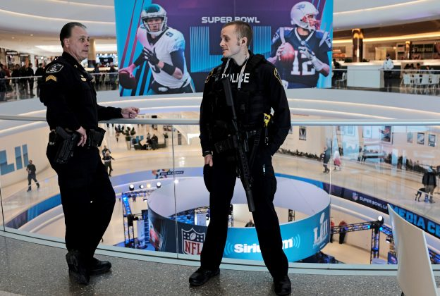 Policemen talk as a Super Bowl promotional banner showing Philadelphia Eagles quarterback Nick Foles and New England Patriots quarterback Tom Brady hangs in an atrium at the Mall of America in Minneapolis, Minnesota, U.S. January 29, 2018