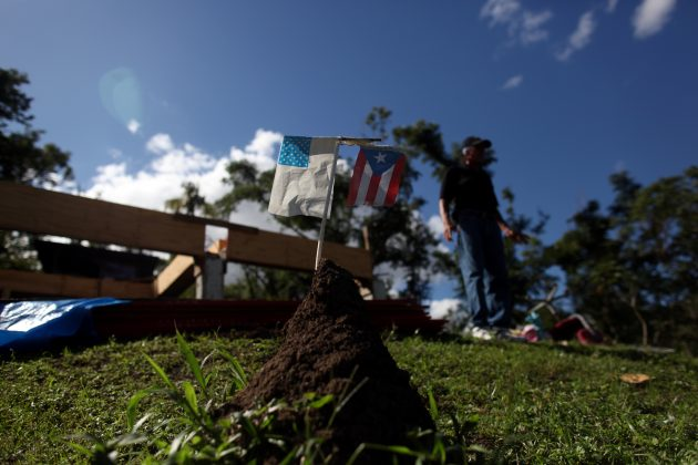 Faded U.S. flag and Puerto Rican flag are stuck into a mound of earth near the remains of Angel Colon's house after it was destroyed during Hurricane Maria in September 2017, in Comerio, Puerto Rico