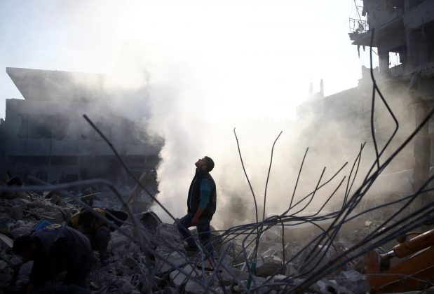 A man stands on rubble of damaged buildings after an airstrike in the besieged town of Hamoria, Eastern Ghouta, in Damascus, Syria Janauary 9, 2018.