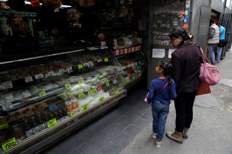 A woman and a child look at prices in a grocery store in downtown Caracas, Venezuela March 10, 2017.