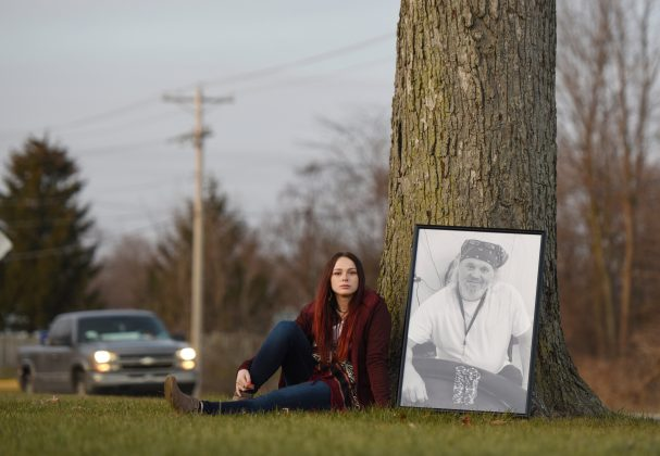 Taylor Wiggington sits with a photo of her father, Doug Wiggington, in the area where he was shocked by a Taser on May 12, 2017, in Greenfield, Indiana, U.S., December 21, 2017.