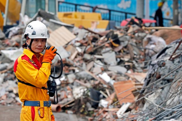 A rescuer speaks on the radio as he searches for survivors at collapsed building after an earthquake hit Hualien, Taiwan February 8, 2018.