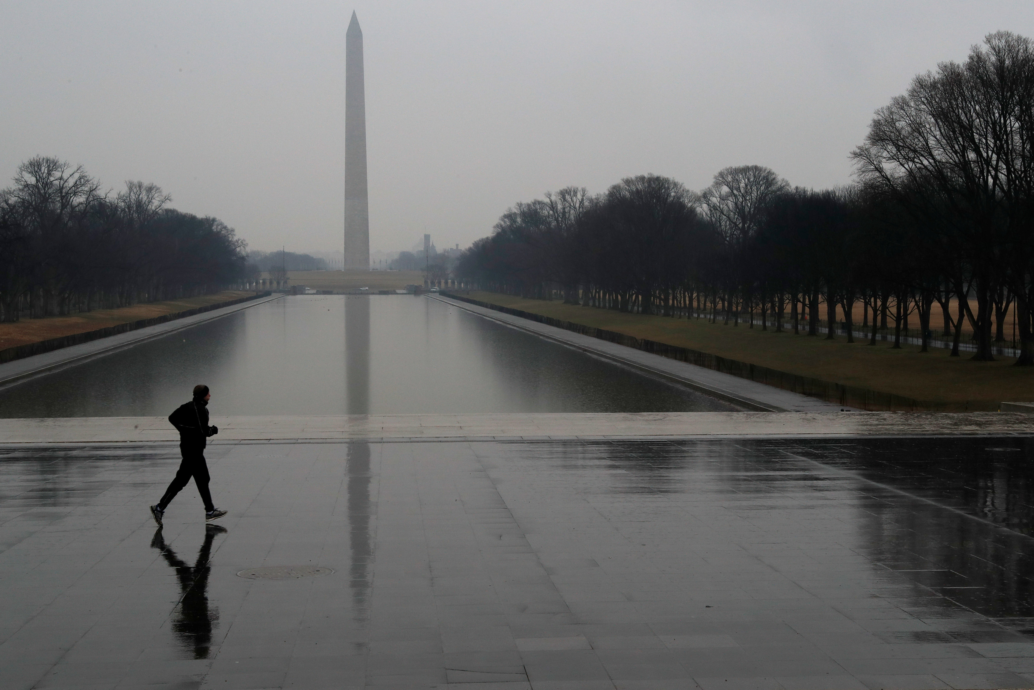 A jogger runs through the rain past the reflecting pool at the Lincoln Memorial in Washington, U.S., February 7, 2018.