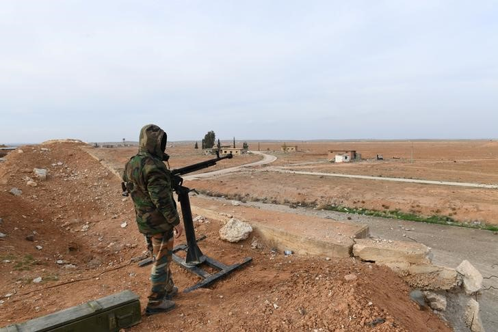 A Syrian Army soldier loyal to Syria's President Bashar al-Assad forces stands next to a military weapon in Idlib, Syria January 21, 2018. Picture taken January 21, 2018.
