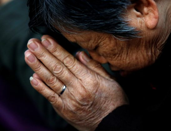A believer prays during a weekend mass at an underground Catholic church in Tianjin in November 10, 2013.