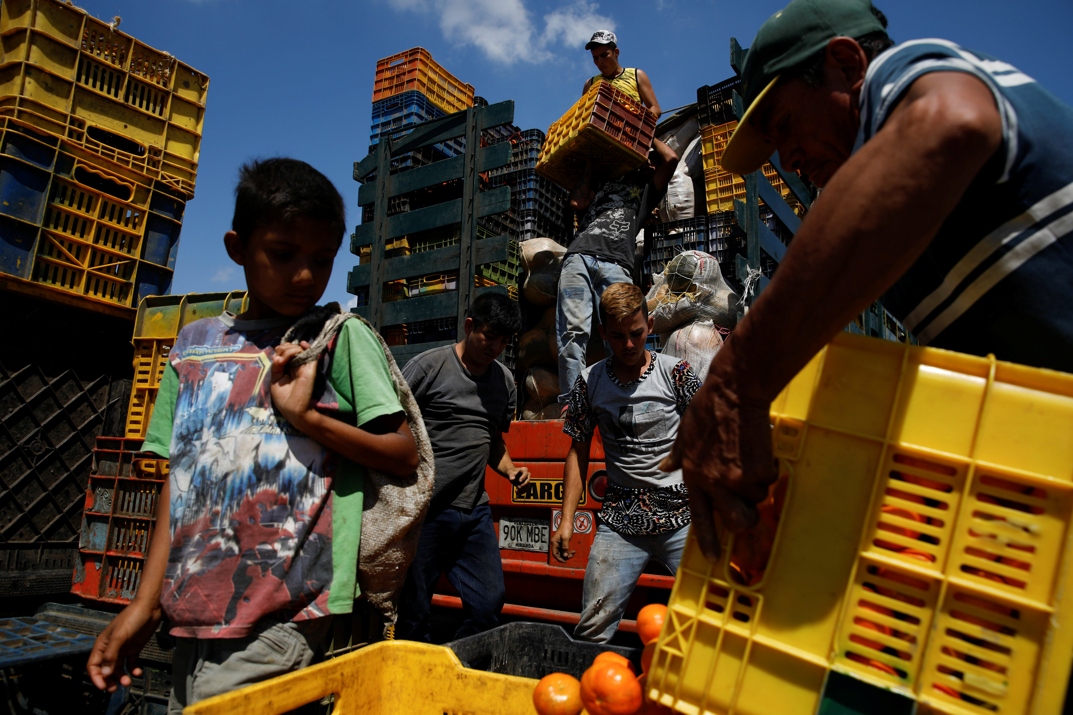 A child looks at a basket filled with mandarins while workers load merchandise into Humberto Aguilar's truck at the wholesale market in Barquisimeto, Venezuela January 30,