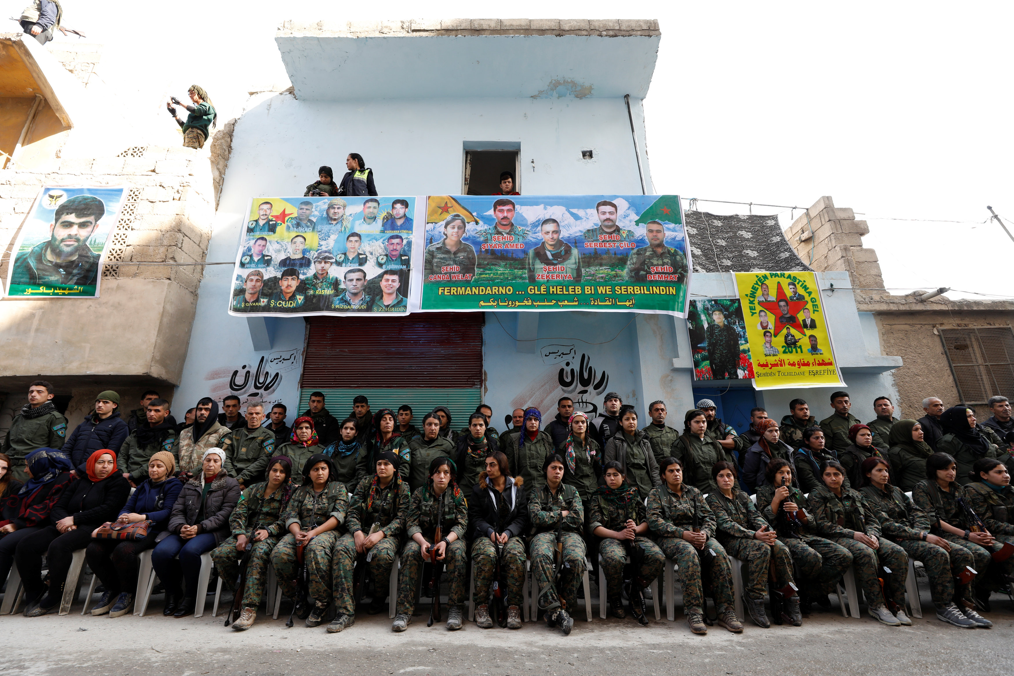 Kurdish female fighters of the Women's Protection Unit (YPJ) hold their weapons as they sit in the Sheikh Maksoud neighbourhood of Aleppo, Syria February 7, 2018. Picture taken February 7, 2018.